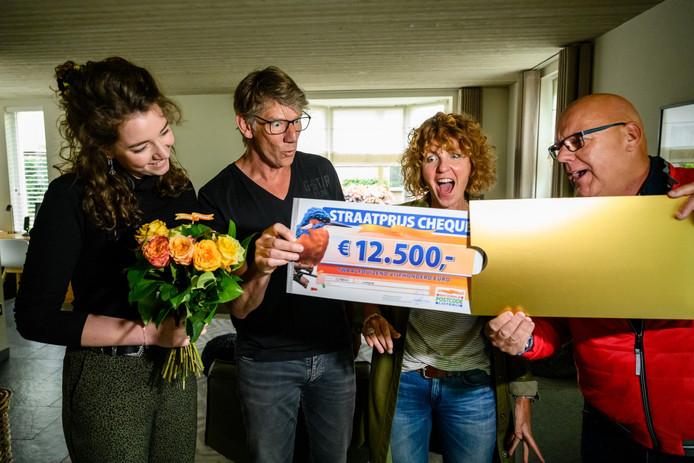 Arthur en zijn gezin worden verrast door Postcode Loterij-ambassadeur Gaston Starreveld met de PostcodeStraatprijs-cheque.