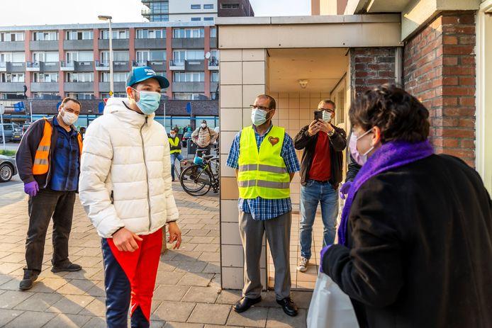 Burgemeester Sharon Dijksma deelt iftarmaaltijden uit aan bewoners van Kanaleneiland. Links, met andere op hun beurt wachtende bewoners, mede-bedenker van de uitdeelactie Karim Ennahachi.