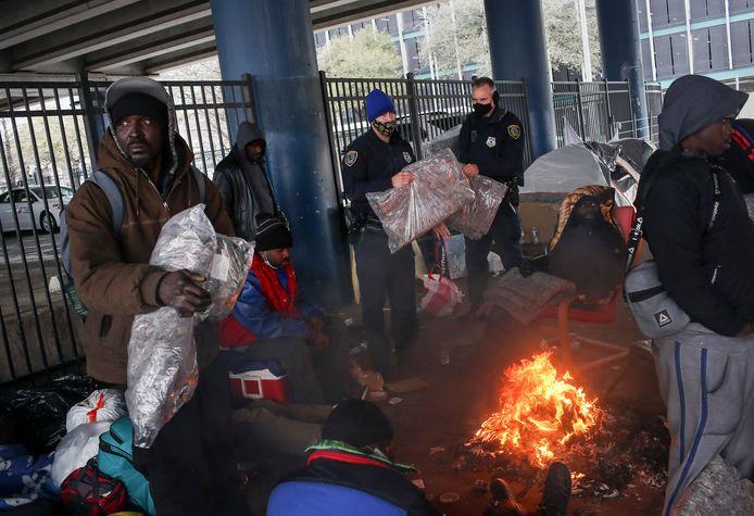 Politieagenten delen dekens uit aan daklozen in Houston, Texas.