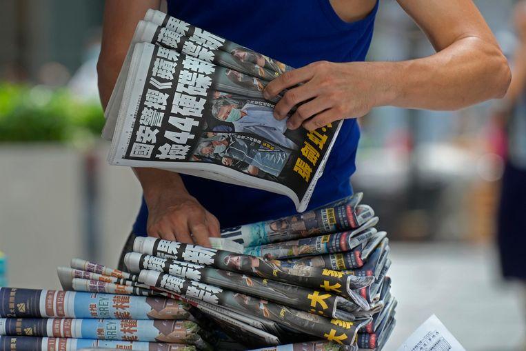Een straatverkoper met een groot pak exemplaren van de Apple Daily. Beeld AP