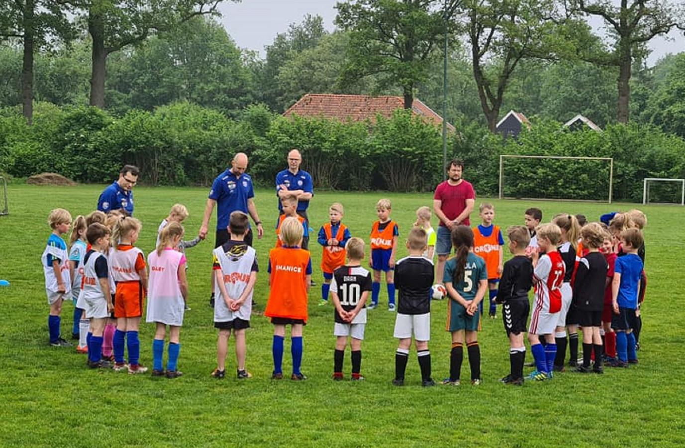 DEO-jeugdspelertjes met collegaatjes van Sportclub Neede op het veld, bij een moment stilte vanwege een overleden Sportclub Neede-lid.
