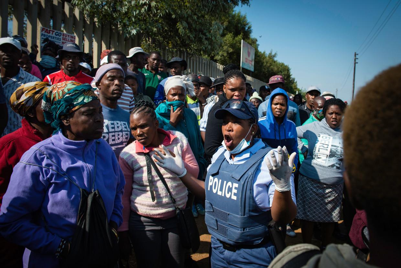 Een politieagent verzoekt de inwoners van township Diepsloot, die in de rij voor voedselhulp, naar huis te gaan.