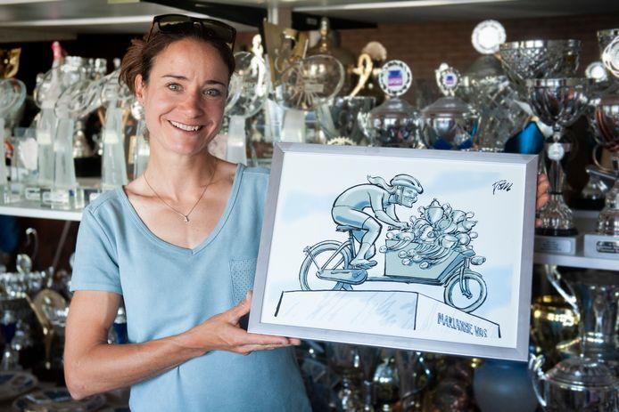 Wielrenster Marianne Vos met een door Tom Janssen gemaakte tekening waarop zij met haar vele trofeeën is uitgebeeld.