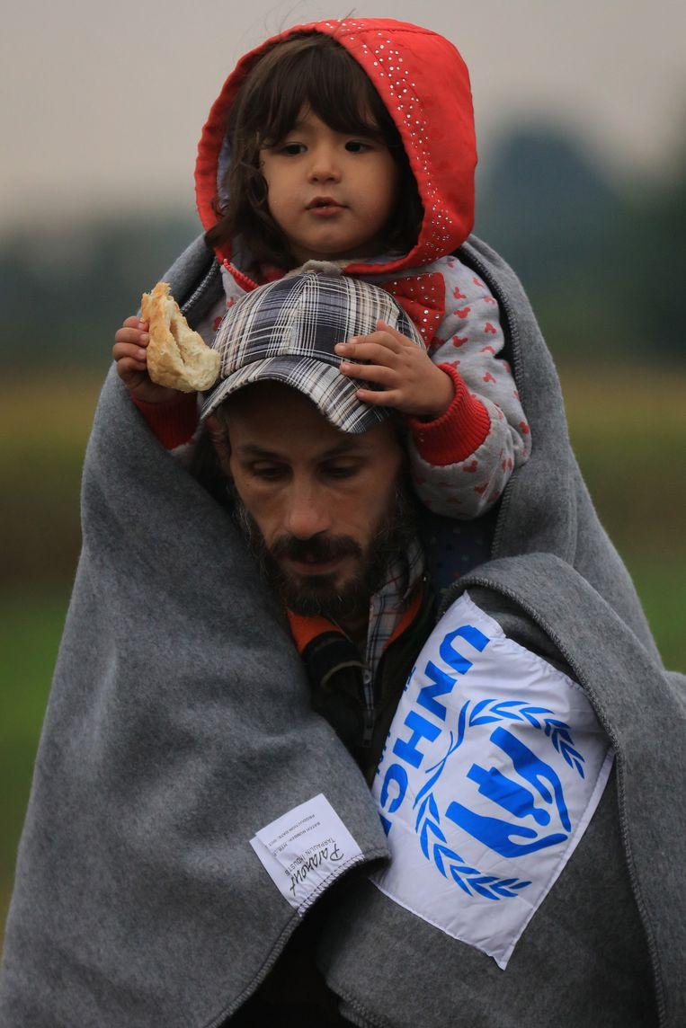 Een vader passeert met zijn dochter de buitengrens van de EU tussen Servië en Hongarije. Beeld getty