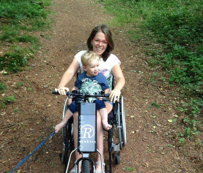 Kim Moorman met zoontje Kick (2) in haar rolstoel, die ze aandrijft met een elektrische handbike.