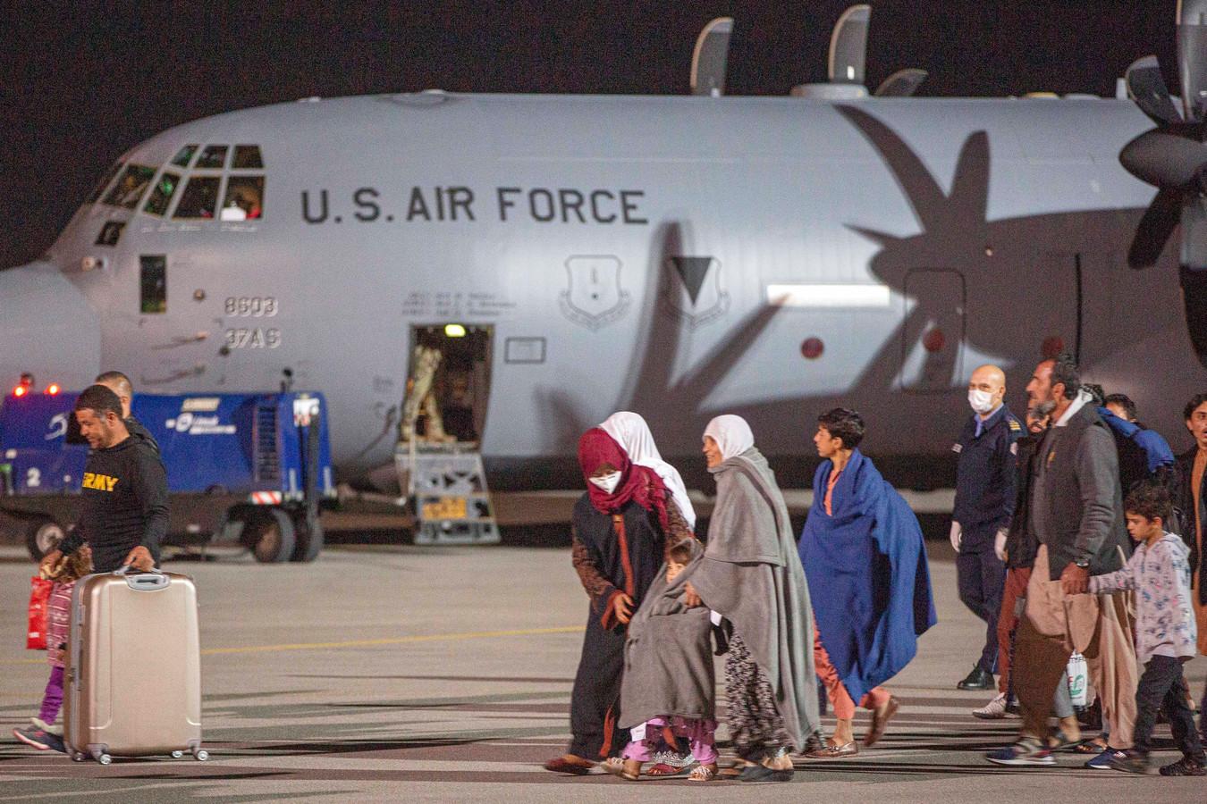 Afghaanse families worden op de luchthaven van Kaboel begeleid naar militaire vliegtuigen.