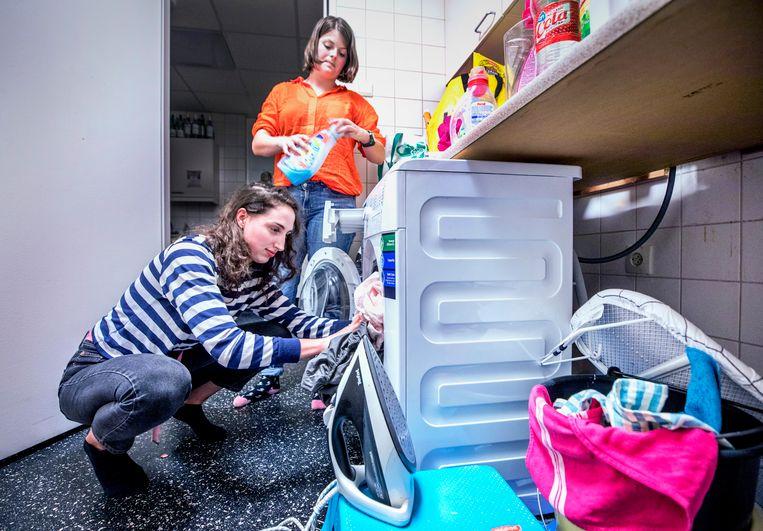 Michèle Brussé (l) vult met een medebewoonster van Huize Rood de leasewasmachine die de studentes 2,40 euro per maand per persoon kost. Beeld Raymond Rutting / de Volkskrant