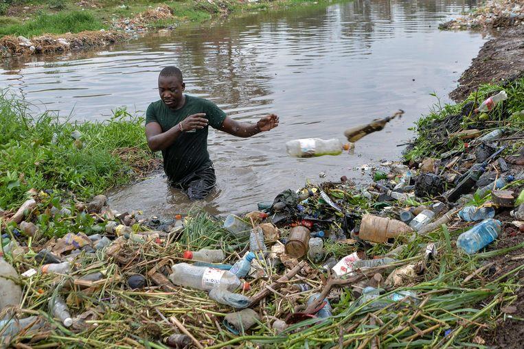 World Cleanup Day vindt over de wereld plaats. In de Keniase plaats Kisumu vist deze man zwerfvuil uit de Wigwa-rivier. Beeld AFP