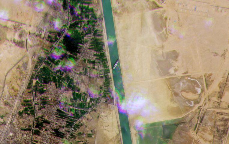 Satellietbeeld van Planet Labs toont van bovenaf hoe verstopt het kanaal nu net is door het gigantische containerschip. Beeld AFP