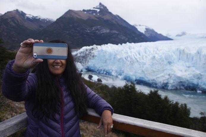 Een toeriste neemt een selfie met de Perito Moreno gletsjer op de achtergrond.