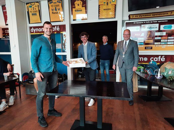 Dynamo-aanvoerder Freek de Weijer neemt een taart in ontvangst van sportwethouder Nathan Stukker en burgemeester Ton Heerts van de gemeente Apeldoorn. Op de achtergrond kijkt Draisma Dynamo-voorzitter Peter de Vries toe.