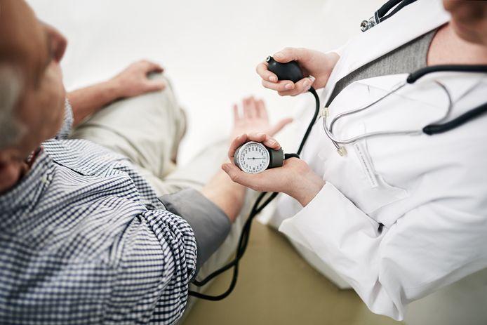 Een huisarts neemt de bloeddruk op.