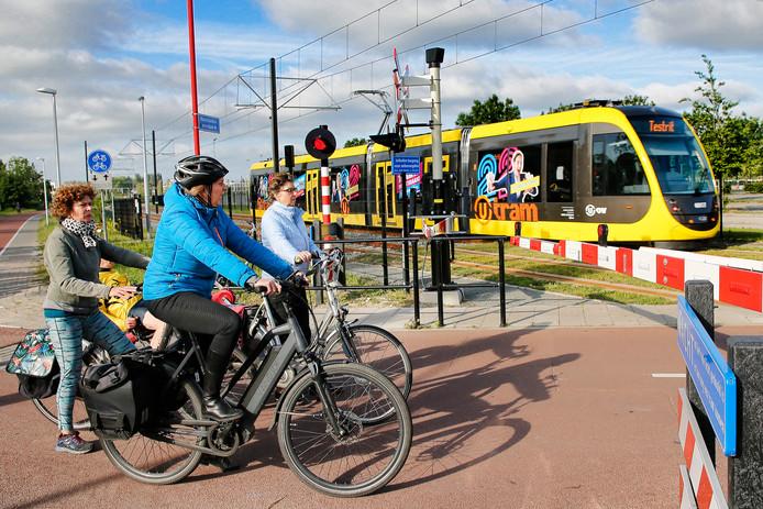Fietsers wachten bij spoorbomen op de Koningsweg op een testrit van de Uithoflijn. Deze lijn brengt veel verandering binnen de nieuwe dienstregeling met zich mee.