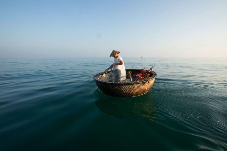 Le Van Hung aan het werk in zijn 'mandboot'. De visser zag het afgelopen jaar al zijn spaargeld verdampen.  Beeld NYT