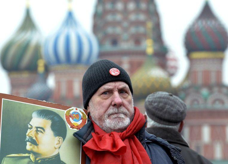 Een aanhanger van de Russische Communistische partij met een poster van Stalin. Beeld afp