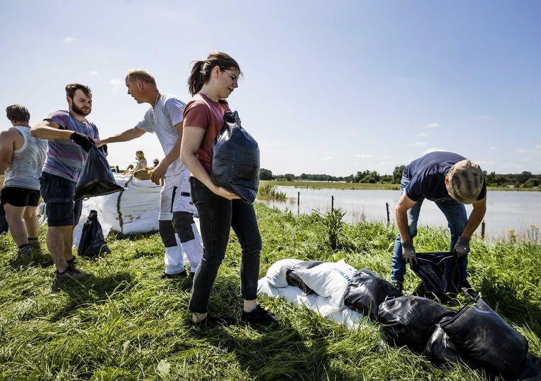 Mensen helpen met het plaatsen van zandzakken net buiten Arcen. (17/07/2021) Beeld ANP