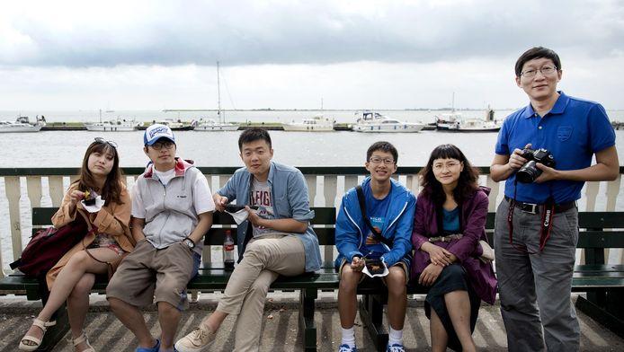 Toeristen eten een visje op de dijk