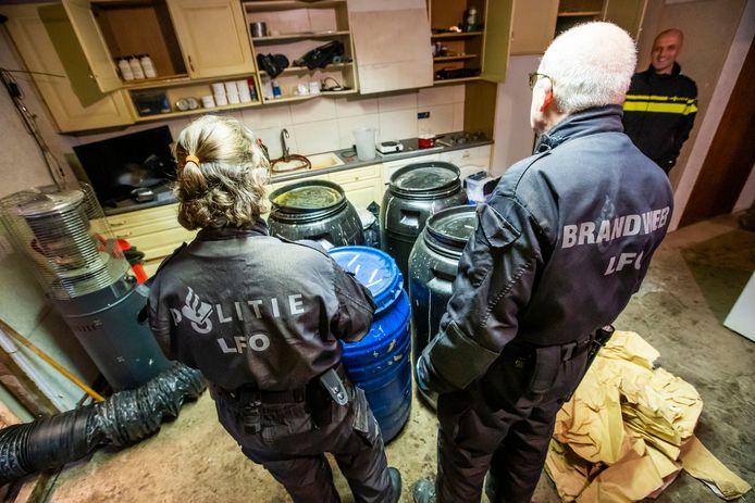 Politie- en brandweermensen in het recent gevonden drugslab in Hapert.