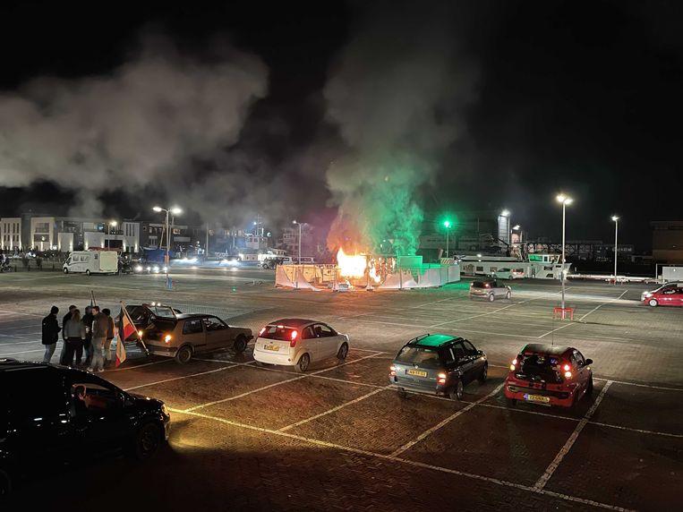 Jongeren staken zaterdagavond de corona-teststraat op het haventerrein in Urk in brand. Beeld ANP
