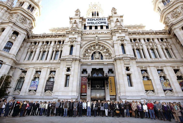 Werknemers van het stadhuis van Madrid houden de 1 minuut stilte voor het gebouw in het centrum van de Spaanse hoofdstad. Beeld epa
