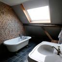 De 'Franse badkamer' met een losstaand bad met gouden pootjes