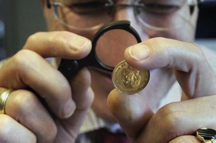 Foto ter illustratie. Inspectie van een gouden tientje.