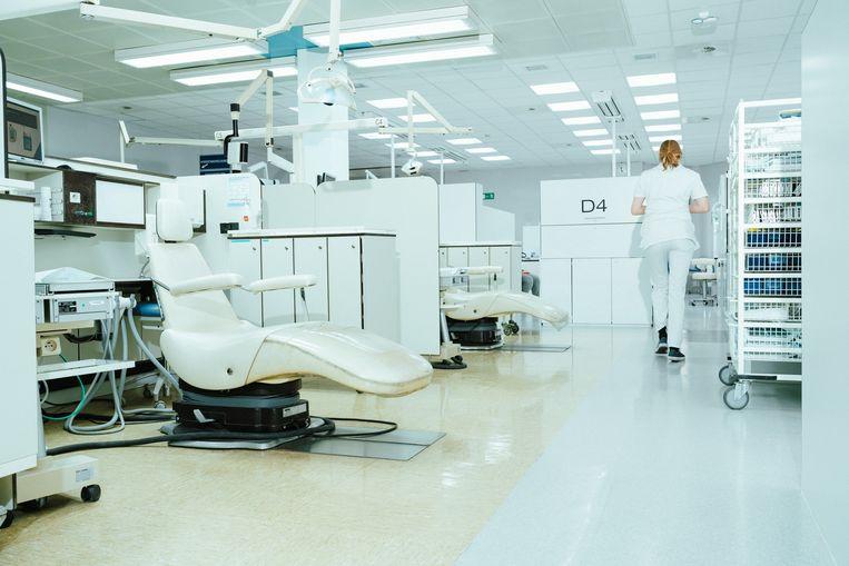 Een absurd gezicht in een laboratorium van de UGent: nieuwe meubels en een strakke witte gietvloer rechts, versleten bureaus en oude tegels links. Beeld Illias Teirlinck