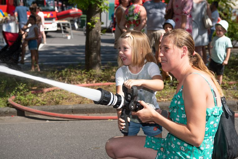 Katrien van Hoorebeke en dochter Louise Naessens (4) aan de slag met de brandweerslang.