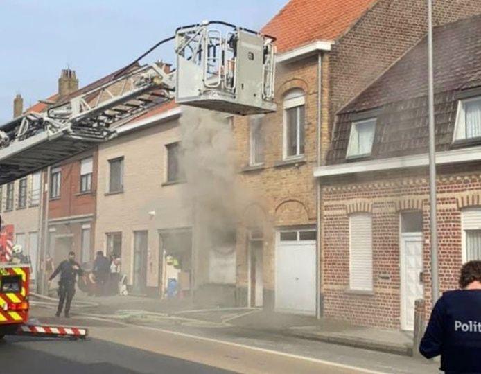 Bij aankomst van de brandweer ontsnappen dikke rookwolken uit de rijwoning langs de Veurnseweg in Brielen (Ieper).