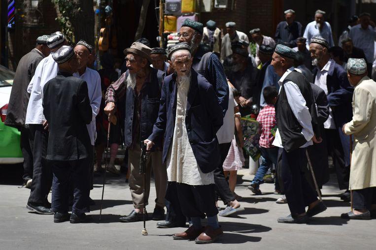 Oude Oeigoerse mannen verlaten hun moskee na het vrijdaggebed in Hotan.  Beeld Greg Baker