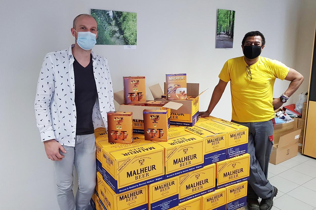 Directeur Wim Kennes nam het bier in ontvangst van een medewerker van Brouwerij De Landtsheer.