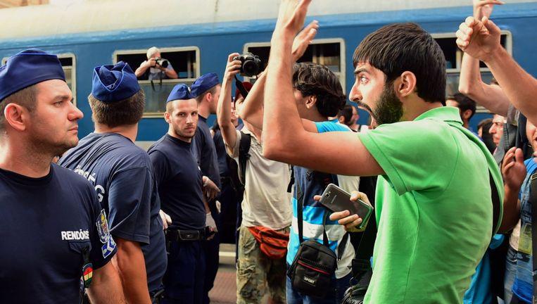 Asielzoekers worden op het perron tegengehouden door de Hongaarse oproerpolitie. Even later mogen ze het station niet meer in. Beeld AFP