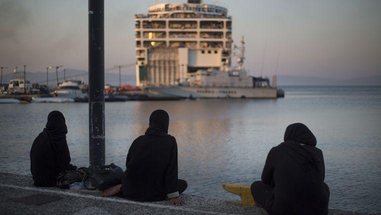 Pakistaanse vrouwen kijken naar de ferry die is aangemeerd in Kos, waarop enkel Syrische vluchtelingen tijdelijk onderdak krijgen Beeld AP