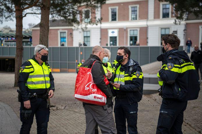 Politie in Apeldoorn stuurde vandaag een groep van ongeveer 50 mensen weg, meldt de gemeente. De man op de foto beledigt deze politiemensen, vinden ze. Hij werd daarom opgepakt.