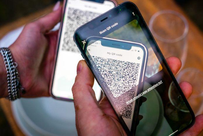 Een mobiele telefoon met de QR code van de CoronaCheck App. De coronapas zal breder ingezet worden om versoepelingen van de coronamaatrdegelen mogelijk te maken.