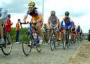 Het peloton raast over de kasseien tijdens de Junioren Driedaagse.