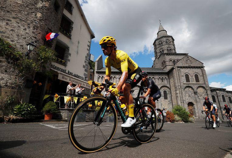 Roglic zoeft door een dorpskern in de Cantal, tijdens rit 13 in de Tour. Beeld REUTERS