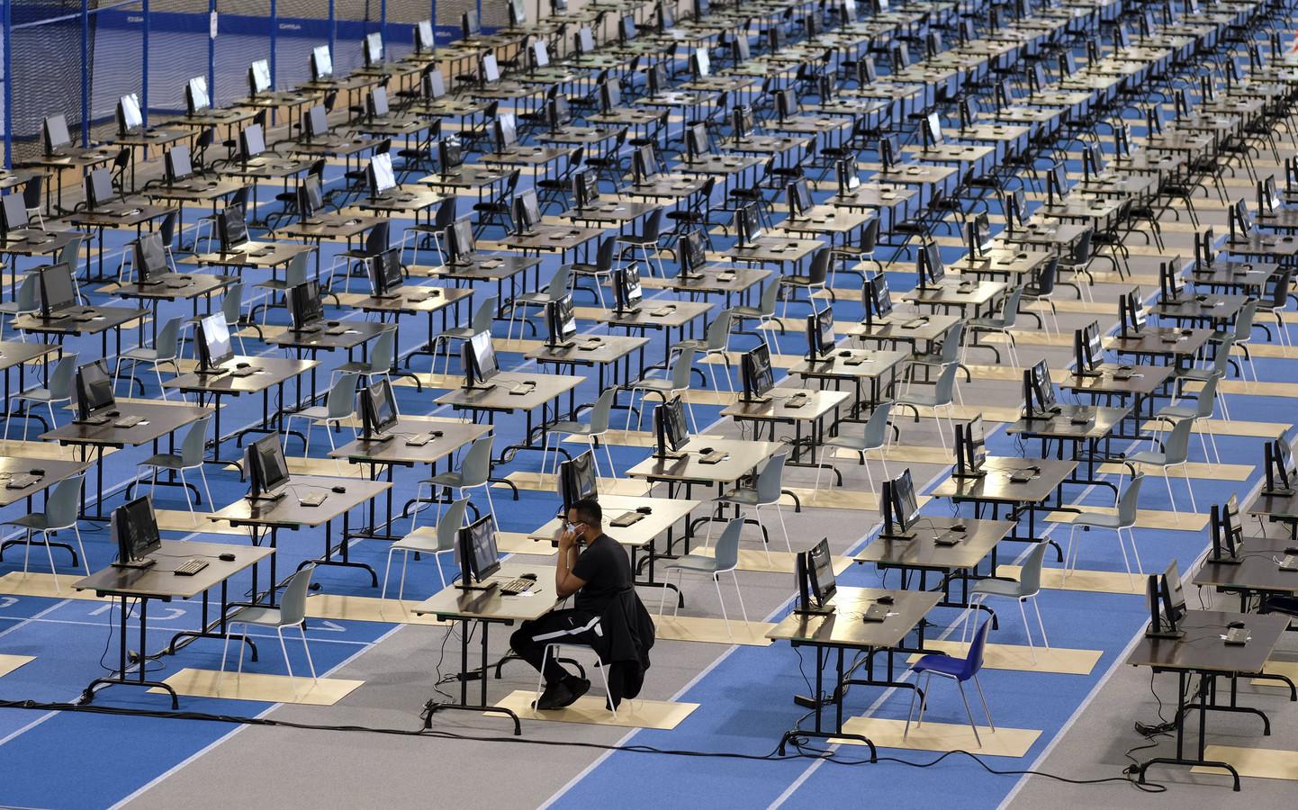 Un étudiant passe un examen seul dans l'immense hall d'athlétisme de Louvain-la-Neuve, juin 2020.