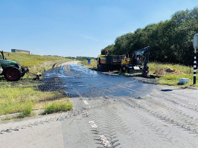 Een vrachtwagen en tractor ruimen het slib op.