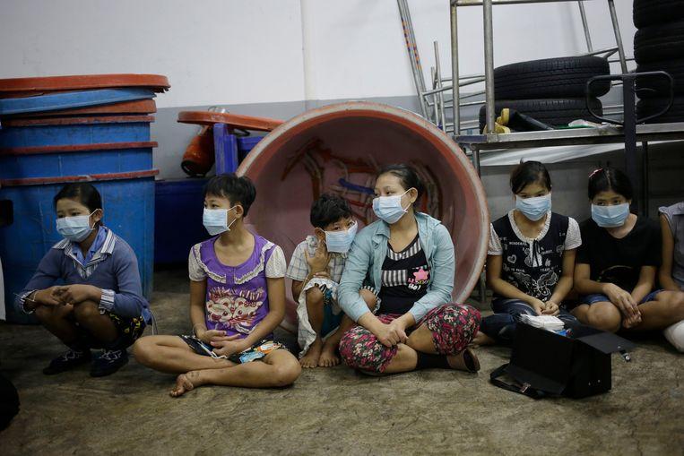 Kinderen en tieners die werden aangetroffen tijdens een inval van door de Thaise autoriteiten in een garnaalfabriek. Beeld AP