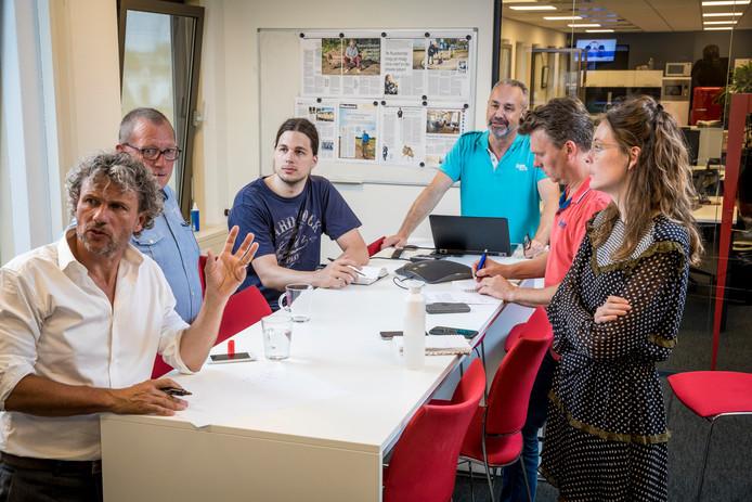 Overleg over de voorpagina van de Stentor. Links hoofdredacteur Allard Besse, die naar een groot tv-scherm kijkt waarop foto's worden getoond die de volgende dag mogelijk de papieren voorpagina van de krant gaan sieren. Onder anderen adjunct-hoofdredacteur Ger Dijkstra (tweede van links) en plaatsvervangend nieuwschef Harmke de Vries (rechts) luisteren toe. Eelco van de Heuvel, chef vormgeving en eindredactie (midden, achter de tafel), presenteert tijdens dit overleg alle mogelijke onderwerpen voor de krant van de volgende dag.