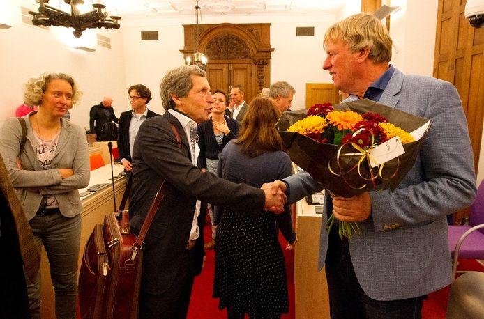 Bert Jansen (links) feliciteert René Sueters met zijn benoeming tot wethouder in de raadszaal in Zutphen.