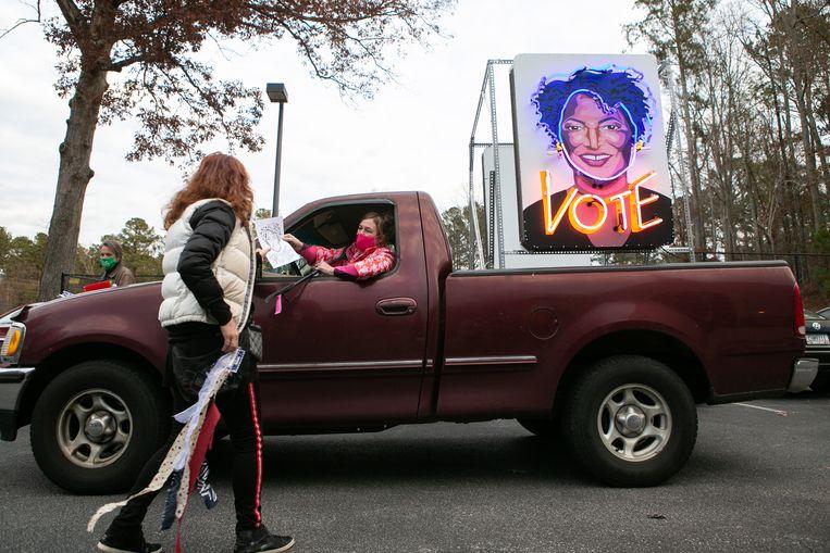 Een Democratische vrijwilliger deelt folders uit waarin mensen worden opgeroepen in januari hun stem uit te brengen bij de tweede ronde van de Senaatsverkiezingen.  Beeld Jessica McGowan / Getty Images
