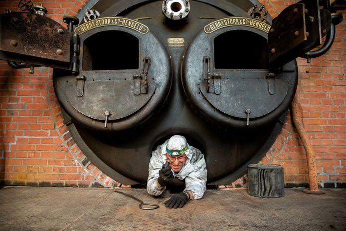 Henk Baan haalt klinknagels uit de ketel in Stoomgemaal de Tuut in Appeltern.