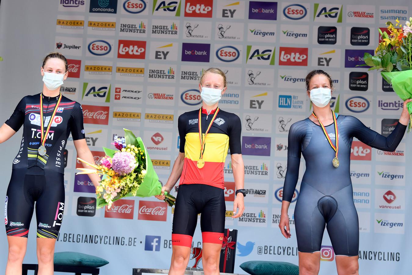 Op het podium voor clubrensters flankeert Julie Sap (r.) kampioene Lotte Claes en zilveren medaillewinnares Fauve Bastiaenssen.
