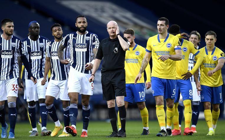 Scheidsrechter Lee Mason heeft weer contact met de Var, terwijl de spelers van West Bromwich (l) en Brighton (r) afwachten op weer een nieuwe beslissing.  Beeld EPA