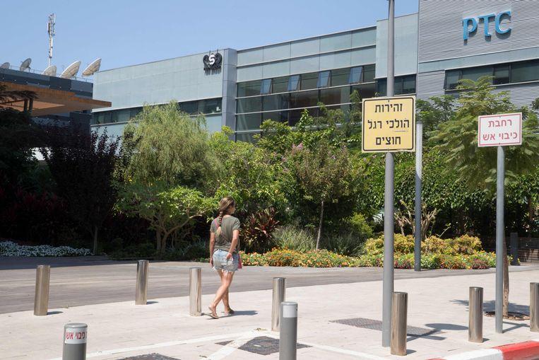 Een vrouw loopt bij het gebouw van het Israëlische NSO group bij Tel Aviv.  Beeld AFP