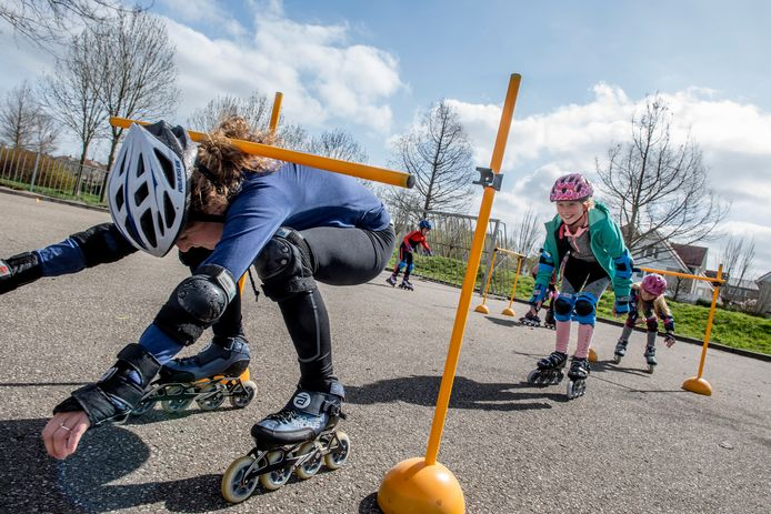 """De deelnemers aan de puzzeltocht van schaats- en skatevereniging Lek en Linge moesten diep door de knieën op het parcourtje met hindernissen aan de Ooievaarslaan. ,,Zo proeven ze even aan een echte skateles"""", zegt Rini van Veen, voorzitter van de club"""