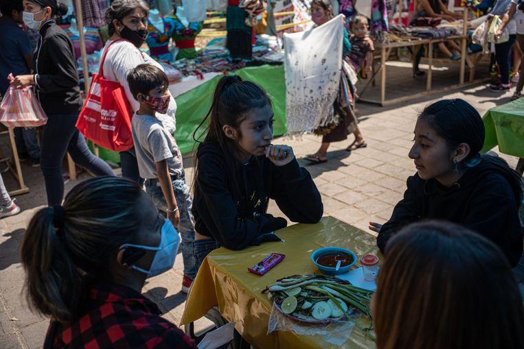 Schoonzussen Ana Mendez en Lorena Reyes wachten op hun tacobestelling met hun dochters Brittany en Ana. Beeld Alejandro Cegarra