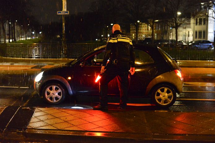 Een agent controleert een automobilist die na 21.00 uur rondrijdt in Breda.
